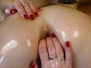 oiled brunette dildoing and fingering both ways